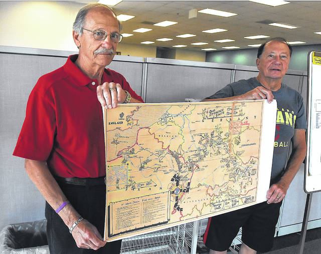 Gary Frueh, left, and his brother, Steve, hold a map of Europe detailing the movements of the Army's 71st Infantry Division, of which their father, Bud, belonged.