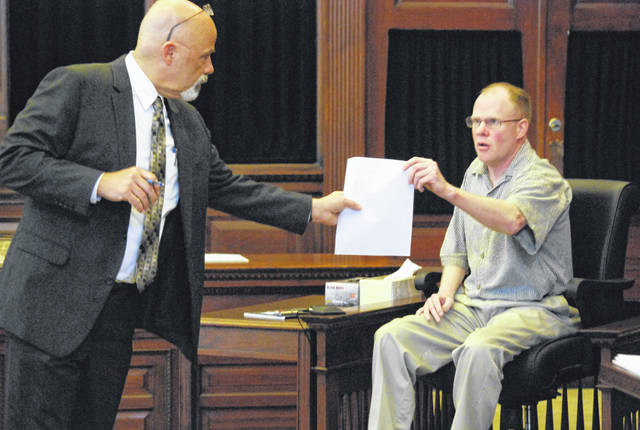 Assistant Prosecuting Attorney Ben Elder, left, exchanges a paper with Brent Williams, accused of murdering his estranged wife, who testified on his own behalf Friday in Auglaize County Common Pleas Court in Wapakoneta.