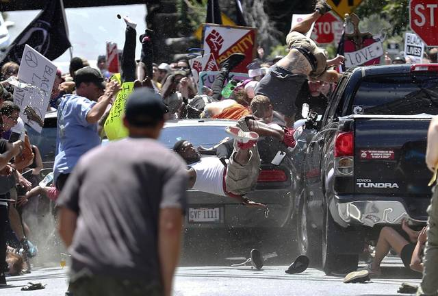 FILE - In this Aug. 12, 2017, file photo, people fly into the air as a vehicle is driven into a group of protesters demonstrating against a white nationalist rally in Charlottesville, Va. James Alex Fields Jr., the man accused of driving into the crowd demonstrating against a white nationalist protest, killing one person and injuring many more, has been sentenced to life in prison on hate crime charges, Friday, June 28, 2019.