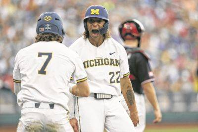 Michigan's Jesse Franklin (7) and Jordan Brewer (22) celebrate after scoring on Jimmy Kerr's two-RBI triple against Texas Tech during the third inning of a Saturday NCAA College World Series game in Omaha, Neb.