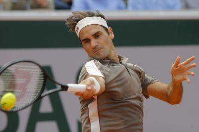 Roger Federer hits a return against Switzerland's Stan Wawrinka during their  French Open quarterfinal match Tuesday at the Roland Garros stadium in Paris (AP photo)