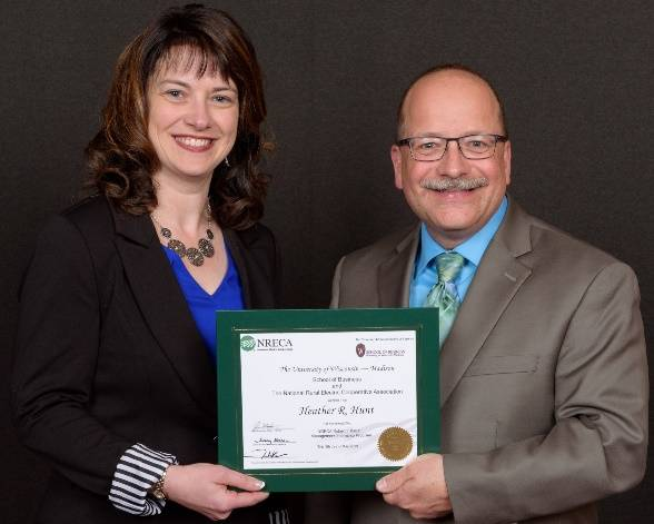 Paulding Putnam Electric Cooperative Human Resources and Administration Manager Heather Hunt accepts her MIP certificate from Gary Pfann, Director of Executive Staff and Education at NRECA, after passing three 10-day sessions.