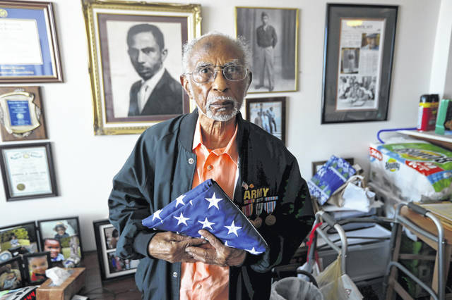 World War II veteran Johnnie Jones, Sr. poses for a portrait at his home in Baton Rouge, La. Jones, who joined the military in 1943 out of Southern University in Baton Rouge, was a warrant officer in a unit responsible for unloading equipment and supplies onto Normandy. He remembers wading ashore and one incident when he and his fellow soldiers came under fire from a German sniper. He grabbed his weapon and returned fire along with the other soldiers. It's something that still haunts his memories. (AP Photo/Gerald Herbert)