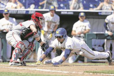 Michigan's Jordan Nwogu scores on a single by Jesse Franklin as Texas Tech catcher Braxton Fulford awaits the throw Friday during a College World Series game in Omaha, Neb. (AP photo)