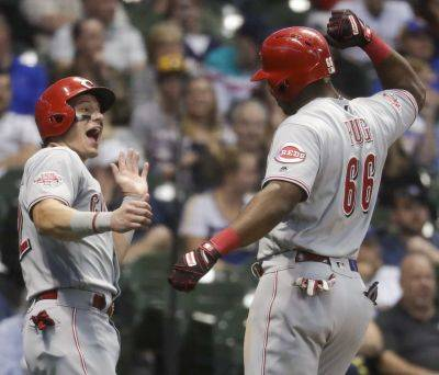 Cincinnati's Derek Dietrich celebrates with teammate Yasiel Puig after Puig hit a two-run home run during Friday night's game against the Brewers in Milwaukee. (AP photo)