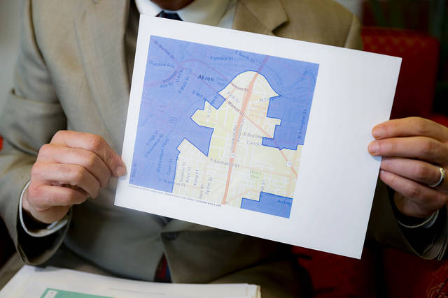 FILE - In this Thursday, April 11, 2019, file photo David Niven, a professor of political science at the University of Cincinnati, holds a map demonstrating a gerrymandered Ohio district. The Supreme Court said, by a 5-4 vote on Thursday, June 27, 2019, that claims of partisan gerrymandering do not belong in federal court. The court's conservative, Republican-appointed majority says that voters and elected officials should be the arbiters of what is a political dispute. The decision effectively reverses the outcome of rulings in Maryland, Michigan, North Carolina and Ohio, where courts had ordered new maps drawn.