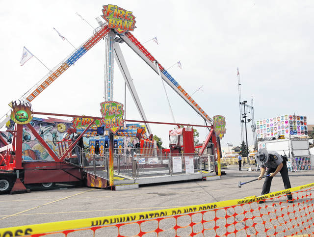 FILE - In this July 27, 2017 file photo, an Ohio State Highway Patrol trooper removes a ground spike in front of the fire ball ride at the Ohio State Fair in Columbus, Ohio after the thrill ride broke apart and killed an 18-year-old man at the Ohio State Fair. A lawsuit filed Monday, June 3, 2019 against Dutch manufacturer KMG, the maker of the amusement ride, says the company knew years before about a defect that caused the deadly crash. The family of an 18-year-old who died at the fair and three others who were seriously injured in 2017 filed the lawsuit Monday against Dutch manufacturer KMG.