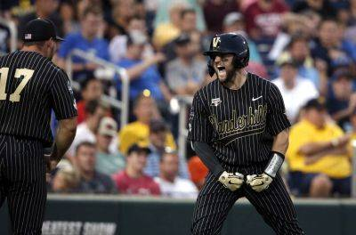Vanderbilt's Philip Clarke celebrates his solo homer with Walker Grisanti (17) in the seventh inning Tuesday night against Michigan in Game 2 of the NCAA College World Series finals in Omaha, Neb. (AP photo)