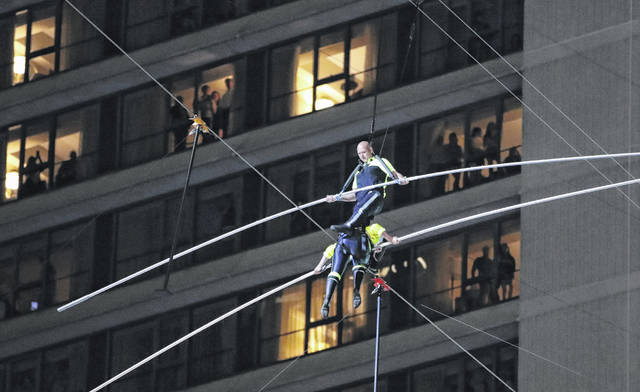 "Nik Wallenda said his pole slipped as his sister knelt so he could step over her while they crossed paths 25 stories above the pavement in Times Square. New Yor ""It freaked me out for a second"" — though his voice and facial expression remained outwardly calm during riveting close-ups shown on television. (AP Photo/Jason Szenes)"