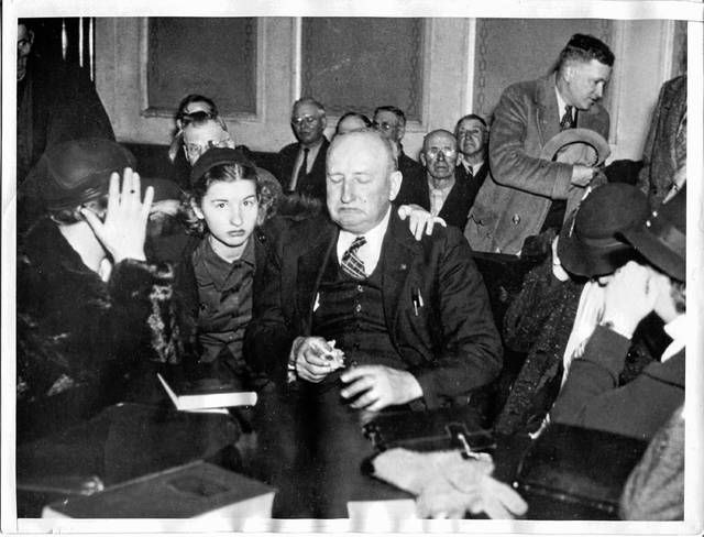 Published Dec. 11, 1937, this photo shows Virgil H. Effinger, 64, reputed commander of the Black Legion, weeping in a Lima court as a judge denied a habeas corpus writ, asked by Effinger's attorneys. But smiles replaced tears as the judge granted a stay of execution on the extradition order, pending appeal to higher courts. Effinger's 16-year-old daughter, Betty, is shown above as she attempted to comfort her father during the hearing.
