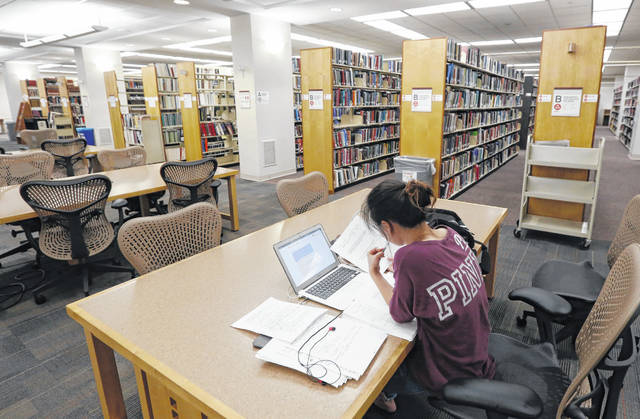 A student works in the library at Virginia Commonwealth University in Richmond, Va., earlier this month. Those who graduate college with student loans owe close to $30,000 on average, according to the most recent data from the Institute for College Access & Success.