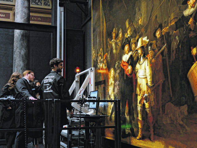 "Technicians and researchers check equipment set up inside a glass chamber as they begin to study Rembrandt's ""Night Watch"" masterpiece, at the Rijksmuseum in Amsterdam on Monday."