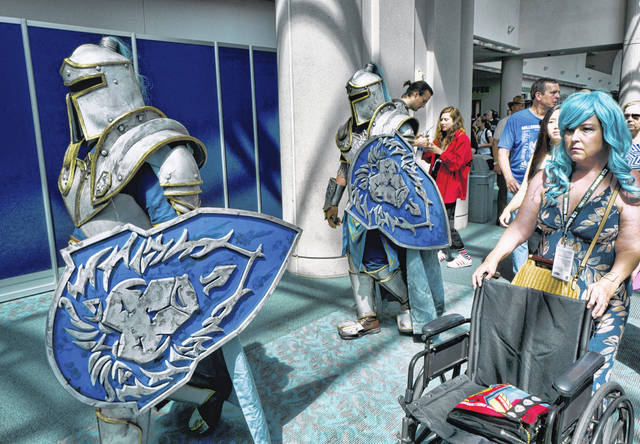 """Attendees Michael Mijerark, left, and Ryan Trent, center, dress as knights from """"Warcraft"""" at Comic-Con International last year in San Diego. The four-day 2019 Comic-Con kicked off Wednesday when the showroom floor opened to thousands vying for exclusive merchandise."""