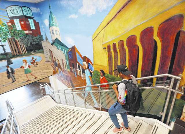 A student walks past a mural in the library at Virginia Commonwealth University in Richmond, Va. College students working a summer job likely shouldn't sweat how it will affect their financial aid: Dependent students can earn up to $6,660 before it increases their expected family contribution, or EFC.