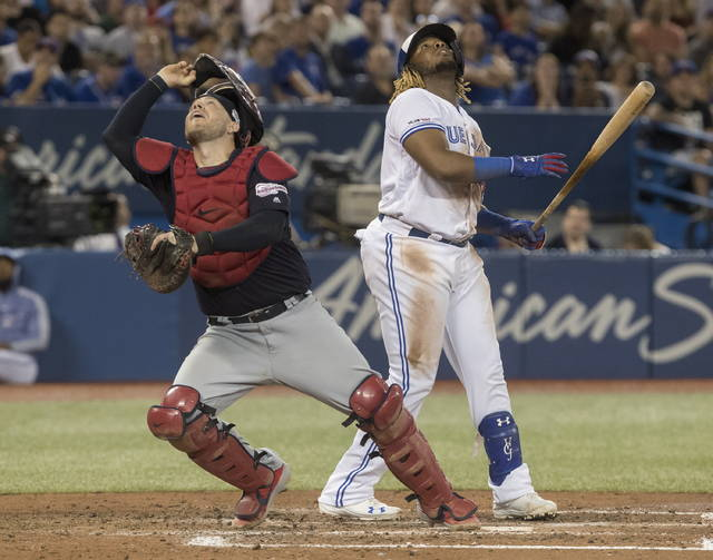 Cleveland Indians catcher Roberto Perez, left, chases a foul ball off the bat of Toronto Blue Jays' Vladimir Guerrero Jr., right, during fourth-inning baseball game action in Toronto, Monday, July 22, 2019. (Fred Thornhill/The Canadian Press via AP)
