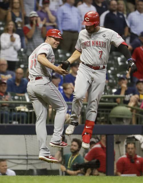 Cincinnati Reds' Eugenio Suarez celebrates his two-run home run with third base/catching coach J.R. House during the ninth inning of a baseball game against the Milwaukee Brewers Monday, July 22, 2019, in Milwaukee. (AP Photo/Morry Gash)