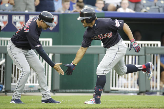 Cleveland Indians' Francisco Lindor celebrates with third base coach Mike Sarbaugh after hitting a solo home run during the first inning of a baseball game against the Kansas City Royals Thursday in Kansas City, Mo. (AP Photo/Charlie Riedel)