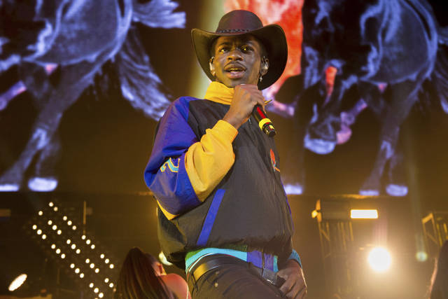 """FILE - This June 1, 2019 file photo shows Lil Nas X performing at HOT 97 Summer Jam 2019 in East Rutherford, N.J. The rapper has taken his """"Old Town Road"""" to the top of the Billboard charts for 16 weeks, tying a record set by Mariah Carey and Luis Fonsi. (Photo by Scott Roth/Invision/AP, File)"""