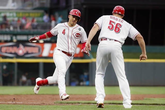 Cincinnati Reds' Jose Iglesias (4) celebrates with third base coach J.R. House (56) while running home to score on a grand slam off Pittsburgh Pirates relief pitcher Montana DuRapau in the second inning of a baseball game, Monday, July 29, 2019, in Cincinnati. (AP Photo/John Minchillo)