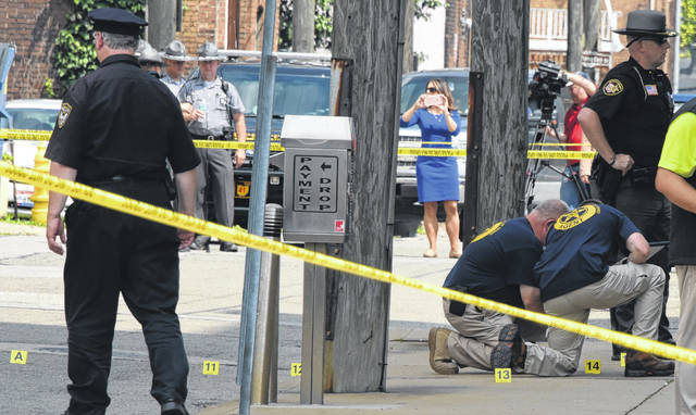 FILE - In this Monday Aug. 21, 2017, file photo, evidence markers are placed on N. Court Street and the sidewalk next to the Jefferson County Courthouse in Steubenville, Ohio, after Jefferson County Judge Joseph Bruzzese Jr. was ambushed and shot earlier in the day. An Ohio appeals court is set to hear arguments, Thursday, July 18, 2019, about whether a surveillance video showing Bruzzese being shot is a public record and should be released to The Associated Press.