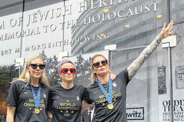 In this Wednesday, July 10, 2019 photo provided by Jeff Simmons, U.S. women's soccer player Ashlyn Harris raises her left arm next to her teammates, Allie Long and Megan Rapinoe, outside the Museum of Jewish Heritage before a victory parade in New York City, to celebrate the team's Women's World Cup title. On Friday, July 19, 2019, The Associated Press reported on stories circulating online incorrectly asserting that Harris is giving a Nazi salute. This photo was made after the museum hosted a breakfast for players before the ticker-tape parade, said Simmons, the executive vice president for Anat Gerstein, Inc., a public relations firm that works with the museum.