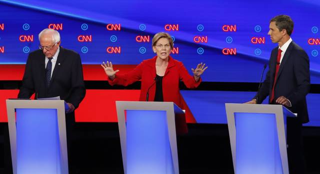 Sen. Elizabeth Warren, D-Mass., speaks as she participates in the first of two Democratic presidential primary debates hosted by CNN Tuesday, July 30, 2019, in the Fox Theatre in Detroit. Sen. Bernie Sanders, I-Vt., left, and former Texas Rep. Beto O'Rourke listen.