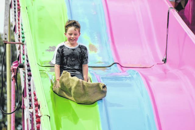 Jefferson Brown, 6, of Cincinnati, slides down the Super Slide Monday at the Auglaize County Fair.
