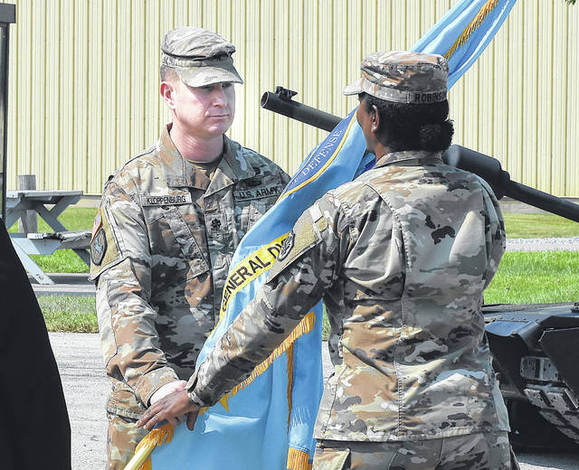 Incoming Commander Lt. Col. George Kloppenburg. left, hands the flag back to Major Tangela Robinson during the change of command ceremony Thursday at the Joint Systems Manufacturing Center.