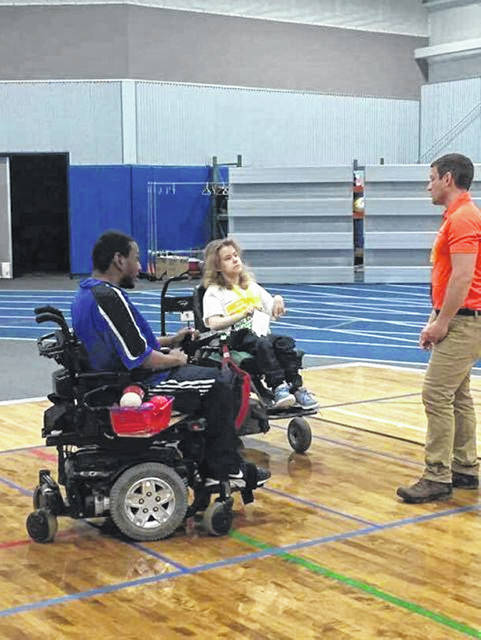 Devin Wolfe (center), of Lima, talks with nationally ranked boccia athlete Marck Harrison (left) and Jason Stubbeman, adaptive athletes coordinator at Synergy Adaptive Athletics, before a boccia tournament in Fort Wayne in April.