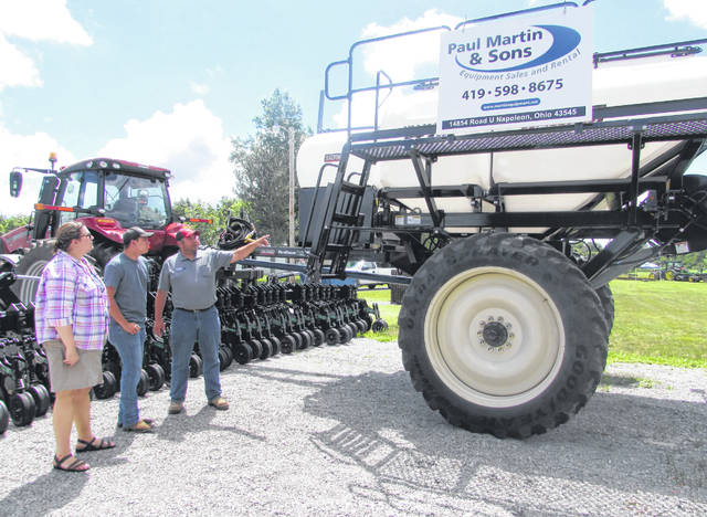 From left are Sarah Fronczak, Hillsdale, Michigan, Tyler Woodbury, Defiance, and Eric Wiemken, Paul Martin and Sons, looking at a nutrient applicator Wednesday at Field to Lake Agriculture Field Day at Kalida Fish and Wildlife Game Club.