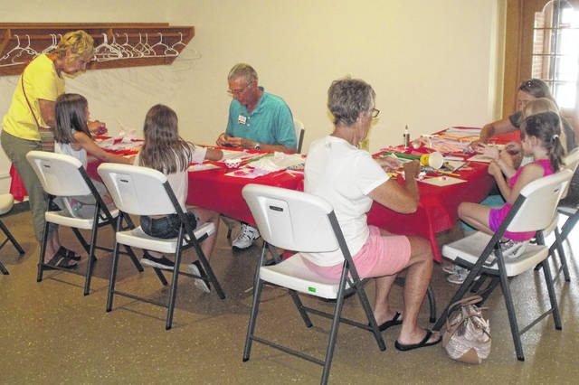 Herb Lauer leads a group of children in quilling, one of the crafts at last year's event.