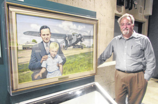 Dante Centuori, Armstrong Air and Space Museum executive director, stands next to a painting of Neil Armstrong at a young age and his dad.