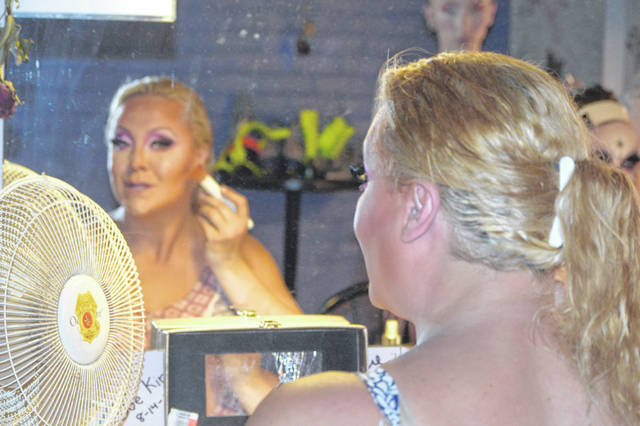 Tyra Brooks, one of the performers at a pride event at Somewhere, applies makeup prior to taking the stage.