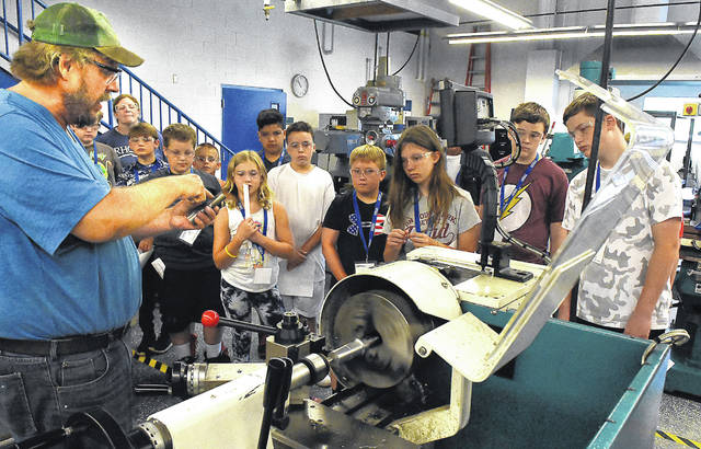 Derek Busboom, left, of Rhodes State, instructs young students about a computerized metal lathe during the first day of a manufacturing camp. The program is to help Allen County students learn about manufacturing, teamwork and local production facilities.