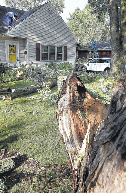 Steve Miller, of 3-M Contracting in Kalida, checks for roof damage after a falling tree struck 1873 Lowell Ave., Lima, on Thursday morning.