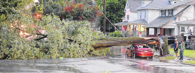 A quick moving storm brought a tree down on an automobile at 721 W. Elm St., on Wednesday evening. More than 4,000 people were without power following the downpour of nearly half an inch of rain.