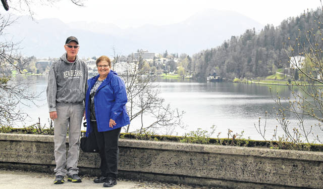 From left are Columbus Grove residents and friends Jerry Bunn and Vicki Doty pictured during their trip in front of Lake Bled in Slovenia.