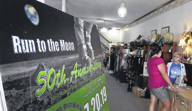 Lynne Skaggs and Judie Presar of Casa Chic Home and Garden display a large poster promoting the 50th Anniversery of the moon landing inside the downtown store in Wapakoneta.  Craig J. Orosz | The Lima News