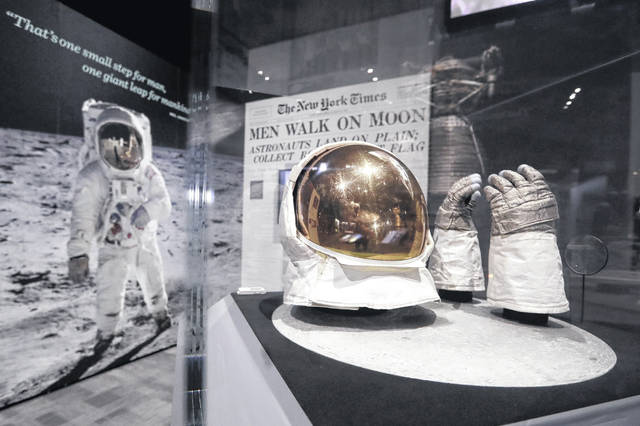 Buzz Aldrin's outer visor and gloves worn while walking on the moon are displayed near a photo of Aldrin at Destination Moon: The Apollo 11 Mission exhibit at the Museum of Flight in Seattle. The exhibit celebrates the 50th anniversary of the U.S. manned moon landing on July 20, 1969. (AP Photo/Elaine Thompson)