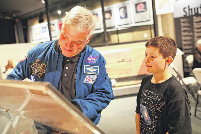 James Schaller, of Perrysburg, gets astronaut Gregory H. Johnson's autograph at an event at the Armstrong Air and Space Museum on Saturday evening.