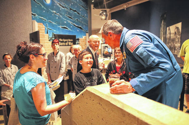 Nine year old James Schaller, of Perrysburg, gets astronaut Michael T. Good's autograph at the dinner held at the Astronaut Dinner Gala held at the Armstrong Air and Space Museum on Saturday evening.