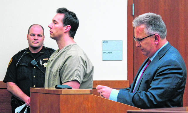 FILE - In this June 5, 2019 file photo former critical care doctor William Husel, center, pleads not guilty to murder charges while appearing with defense attorney Richard Blake, right, in Franklin County Court in Columbus, Ohio. An Ohio hospital system has reached nearly $4.5 million in settlements so far over the deaths of patients who allegedly received excessive painkiller doses ordered by Husel, now charged with murder. Over two dozen wrongful-death lawsuits have been filed against the Columbus-area Mount Carmel Health System and now-fired intensive care doctor William Husel.