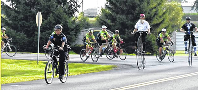 Participants from left Brian Born, Ohio High Wheeler Bicycle Association member, and Daniel Tinch, executive director of Bluffton Family Recreation Center, ride on high wheeler bicyles during last year's event.