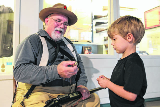 John Carnes portrays a Spanish/American War infantry soldier and shows 4-year-old Calvin Flory a Krag-Jorgenson gun and bullet during the live history event held at the Allen County Museum.