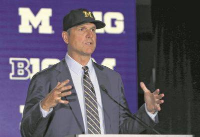 Michigan head coach Jim Harbaugh responds to a question Friday during Big Ten football media days in Chicago. (AP photo)