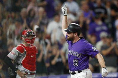 Cincinnati catcher Curt Casali watches as Colorado's Daniel Murphy crosses home plate after hitting a solo home run during the eighth inning of Friday night's in Denver. The Rockies won 3-2. (AP photo)