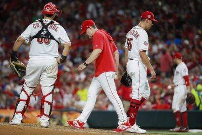 Reds relief pitcher Robert Stephenson (55) is removed by manager David Bell, center, after giving up a grand slam to St. Louis' Tommy Edman during Thursday night's game in Cincinnati. (AP photo)