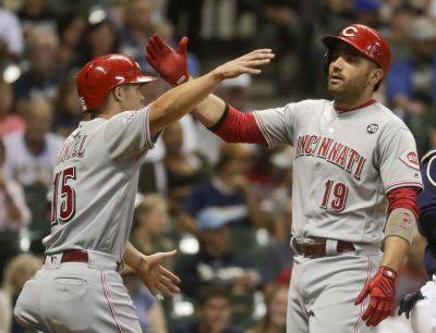Cincinnati's Nick Senzel, left, congratulates Joey Votto on his two-run home run during the sixth inning of Tuesday night's game in Milwaukee. (AP photo)