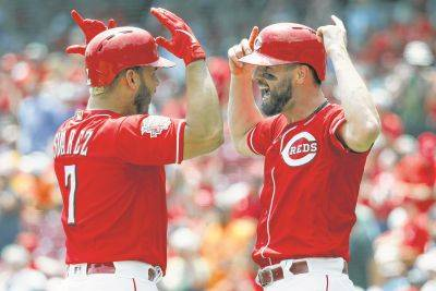 The Reds' Eugenio Suarez, left, celebrates with Jesse Winker after hitting a two-run home run during Wednesday's game against Pittsburgh in Cincinnati.