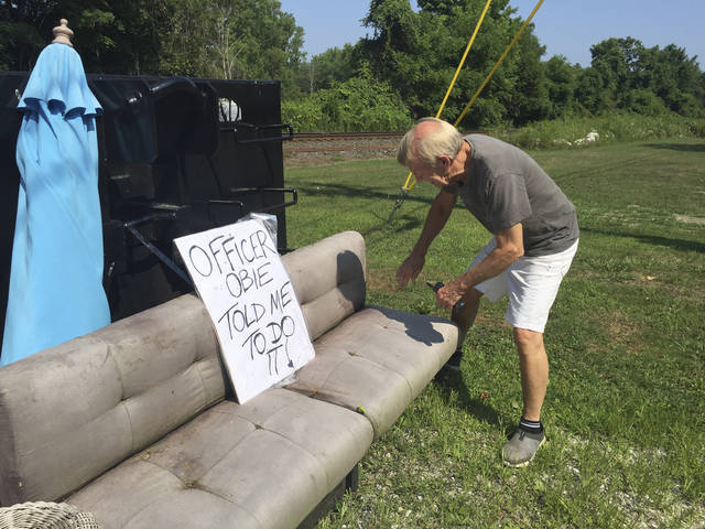 "In this July 30, 2019 photo, Guthrie Center director George Laye searches for clues that might identify the person who dumped an old couch and other refuse in front of the nonprofit's construction bin in Great Barrington, Mass. Whoever dumped the trash at the building made famous in Arlo Guthrie's 1965 Thanksgiving anthem ""Alice's Restaurant Massacree"" has a sense of humor. That person had filled the dumpster with trash and left a grubby sofa nearby, along with a sign that said: ""Officer Obie told me to do it."" (Heather Bellow/The Berkshire Eagle via AP)"